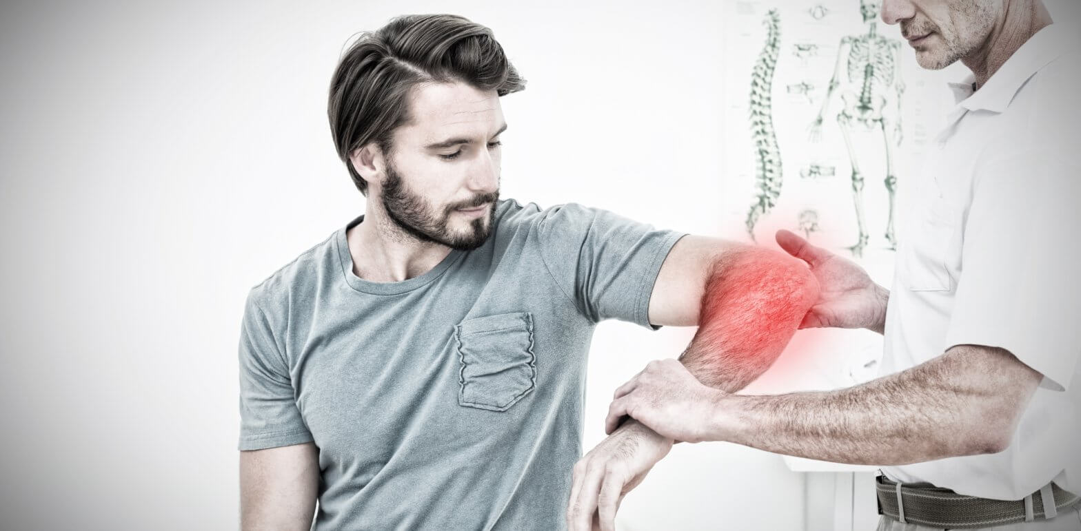 male physiotherapist examining the red, swollen left elbow of a male patient