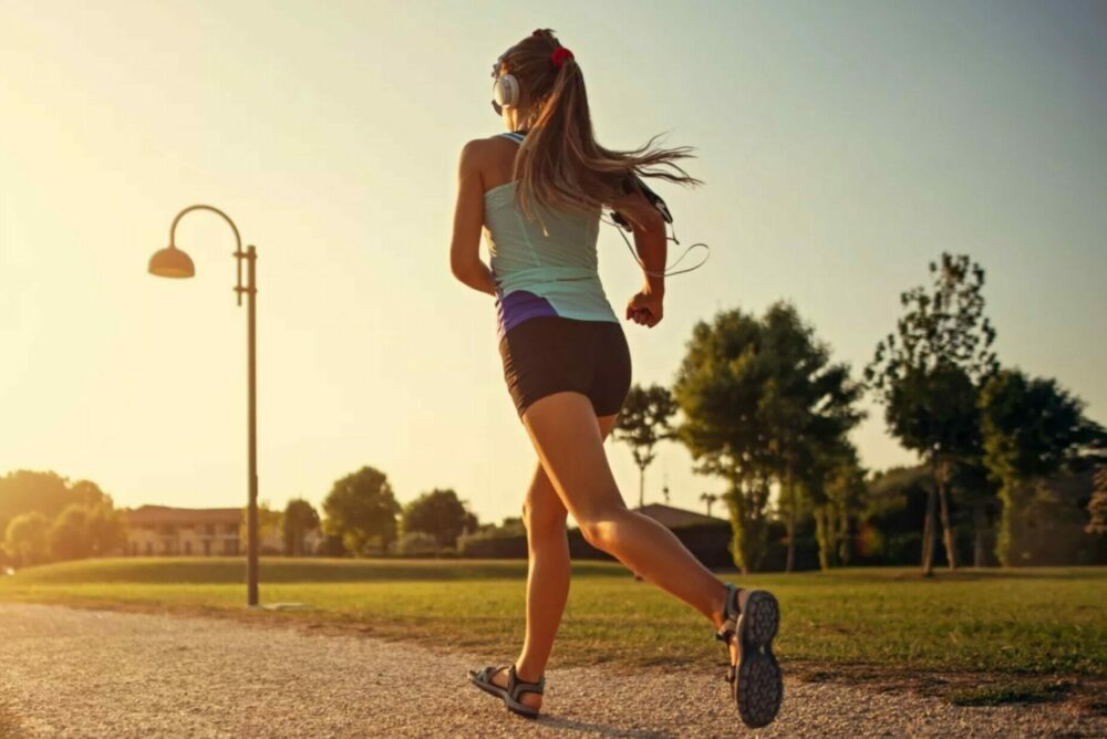 young woman jogging by the light of the evening sun