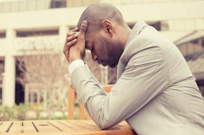 Man sitting at an outdoor table holding his head in pain