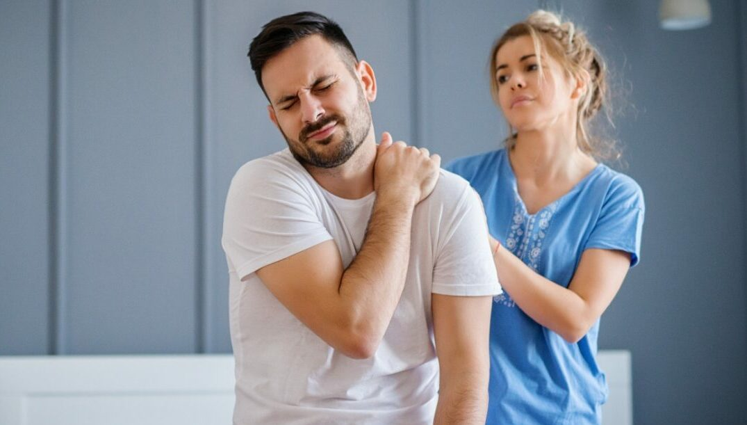 Man sitting up in bed clutching his left trapezius area while his wife tries to help with some massage