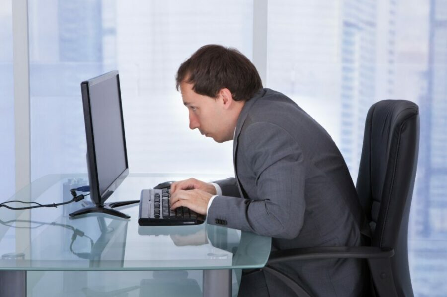 Man sitting at a computer in an office tower with poor posture