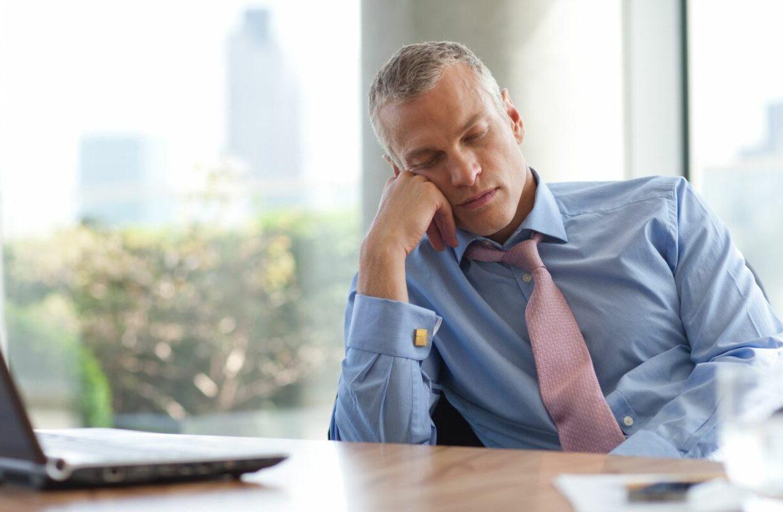 Man in business attire falling asleep at a desk