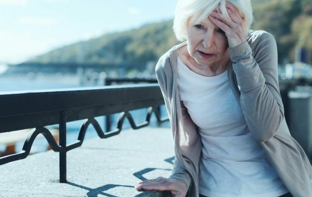 Older female using a concrete wall to steady herself when feeling dizzy