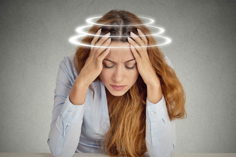 Woman sitting at table with head in her hands and lines indicating dizziness