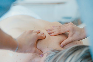 Close up of hands massaging a patients lower neck