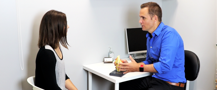 A male physiotherapist performing an initial assessment with a patient at a desk using an anatomical model of the knee joint