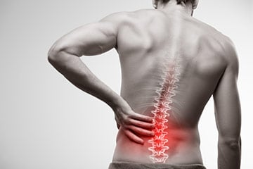A man's back with spinal joints depicted while he clutches his low back in pain
