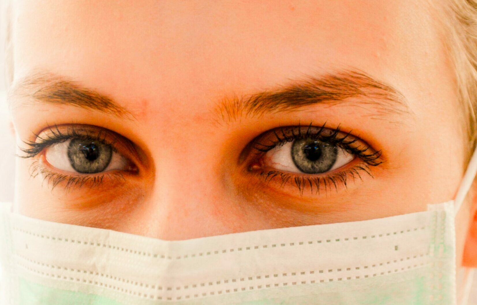 Close up of the face of a woman wearing a surgical face mask