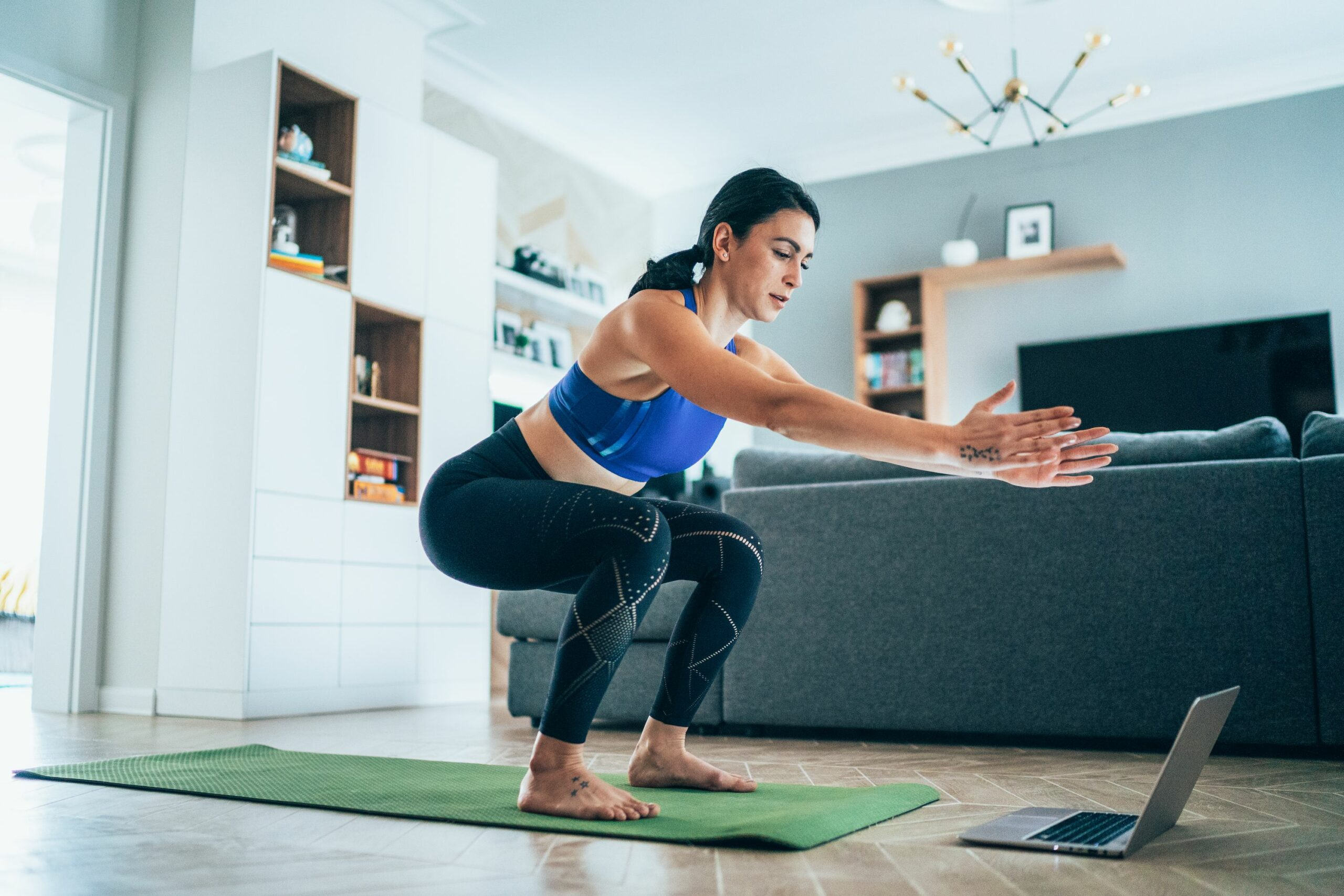 Athletic woman performing a squat in her living room while looking at a laptop screen