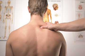 man's back with a hand massaging his right trapezius muscle