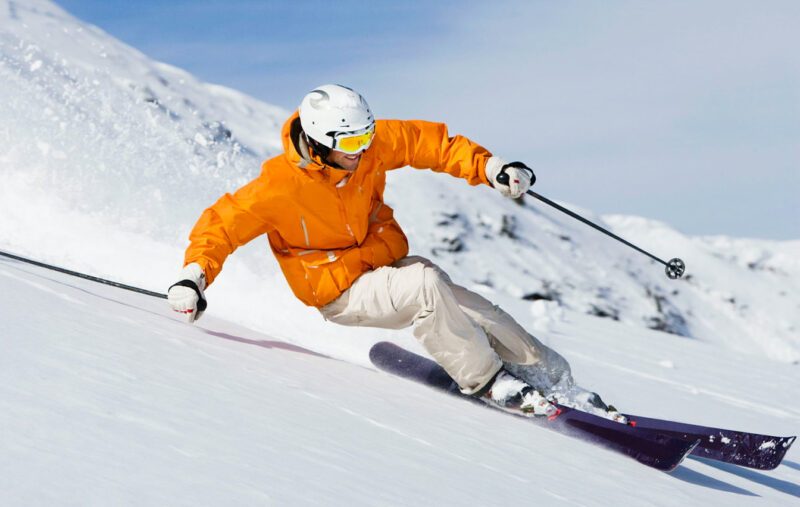 man skiing downhill in orange jacket