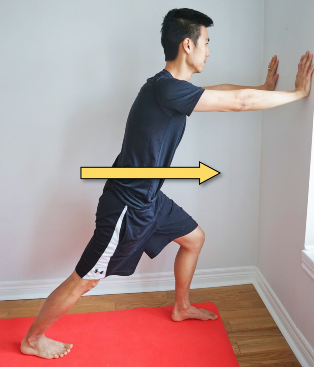 man stretching his calf while leaning forward against a wall