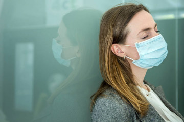 woman wearing a face mask looking fatigued from long-Covid