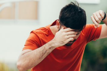 man leaning against wall feeling dizzy due to BPPV